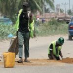 cripple filling potholes lagos road